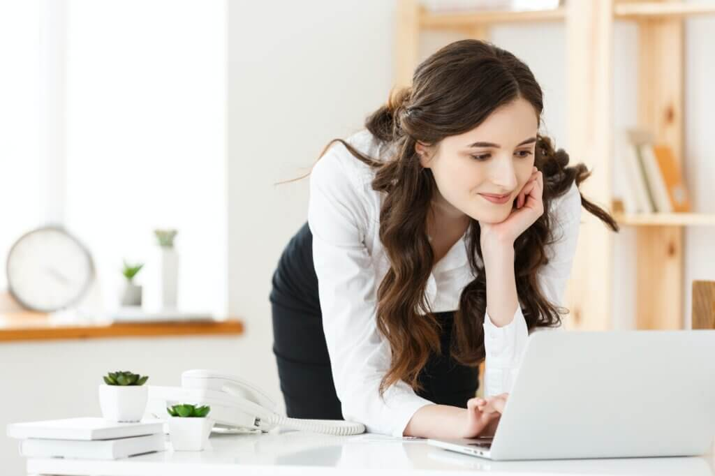 Work from home concept - Beautiful young woman in her home working on laptop. Working at home